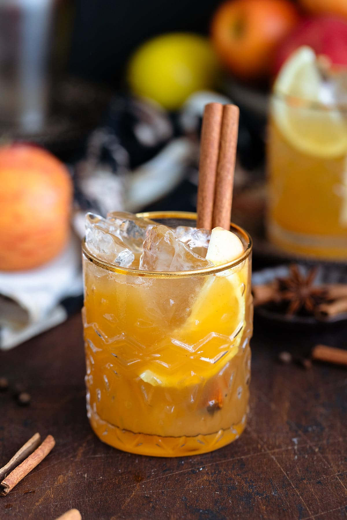 Bourbon cocktail in a glass with a gold rim and garnished with a cinnamon stick on a dark wooden background.