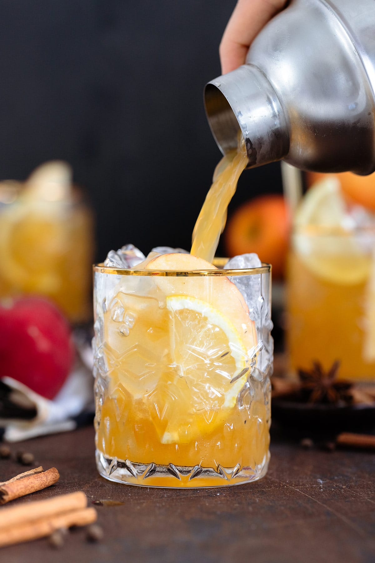Bourbon cocktail being poured over ice into a glass with a gold rim on a dark wooden background.
