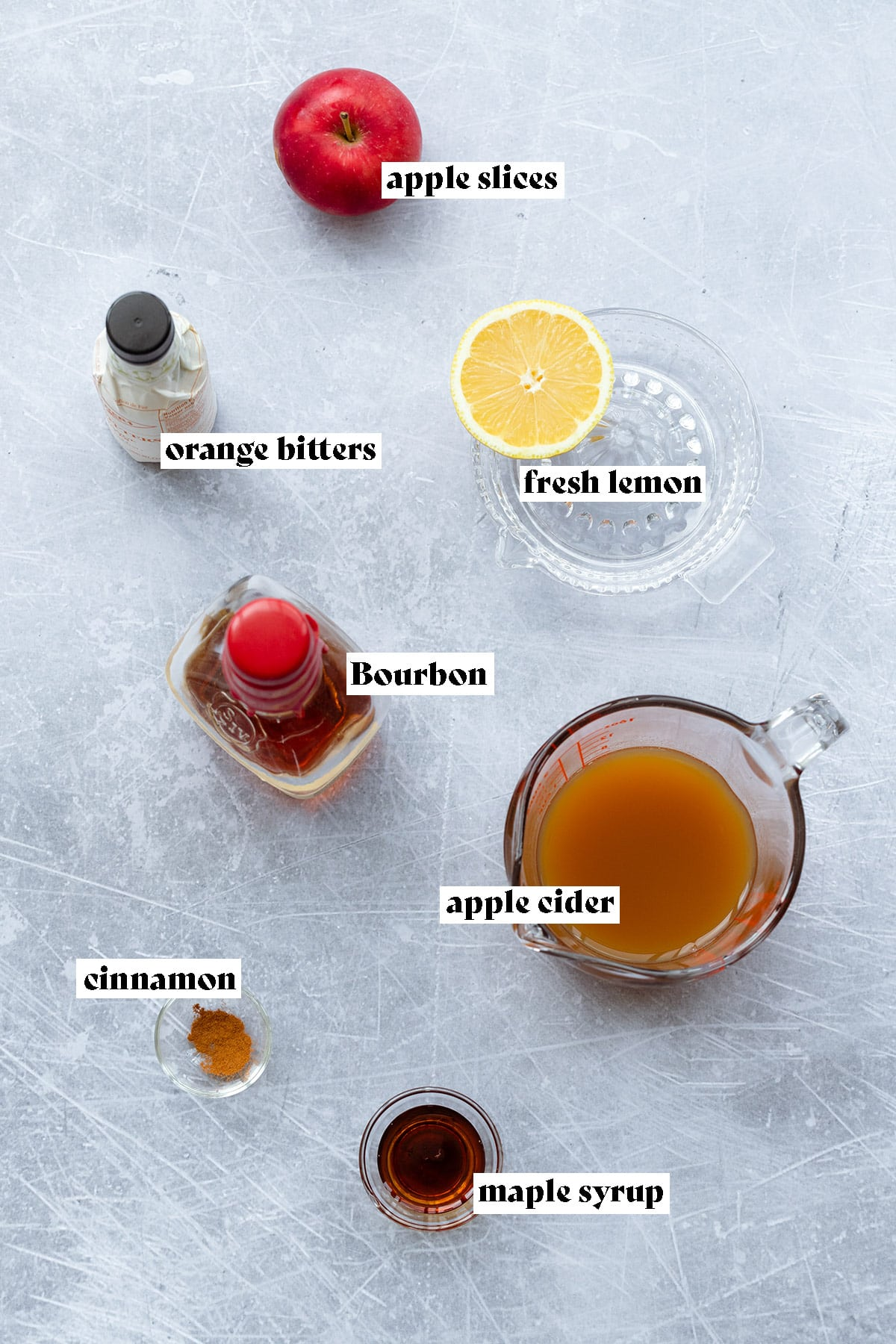 Ingredients for the Bourbon apple cider cocktail laid out on y light metal background.