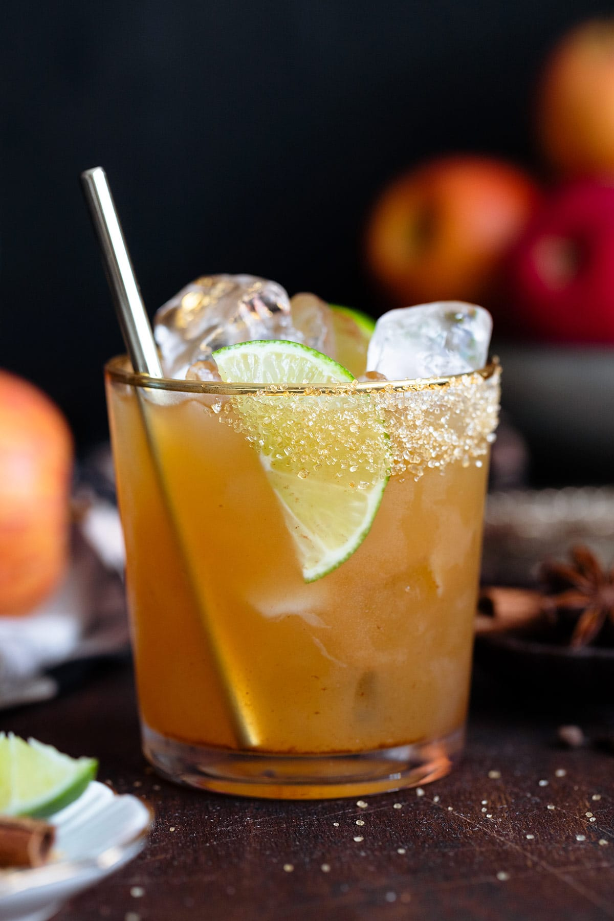 A cocktail in a short glass with a gold rim garnished with a lime slice on a dark wooden background.