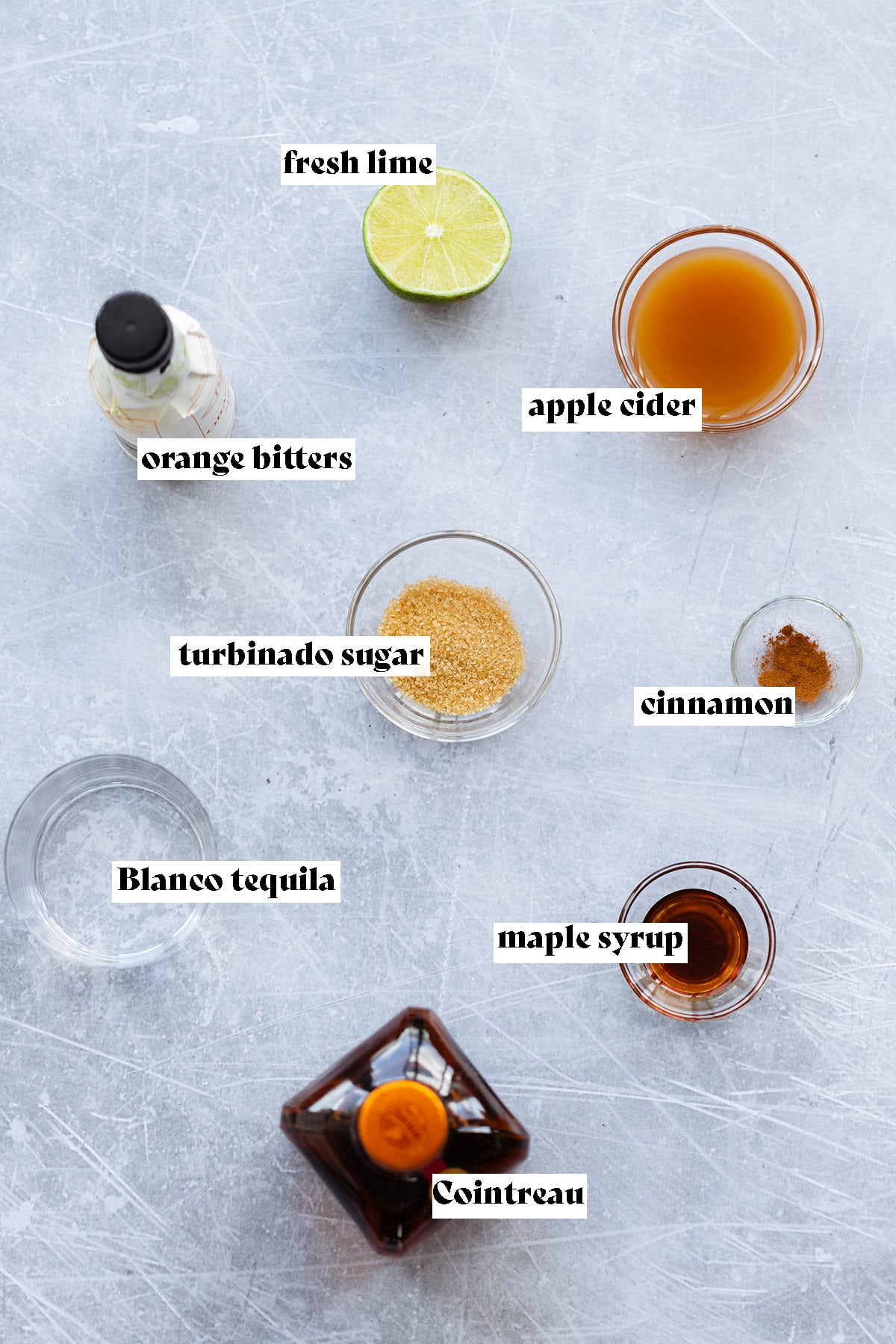Ingredients for apple cider margarita being laid out on a light metal background.