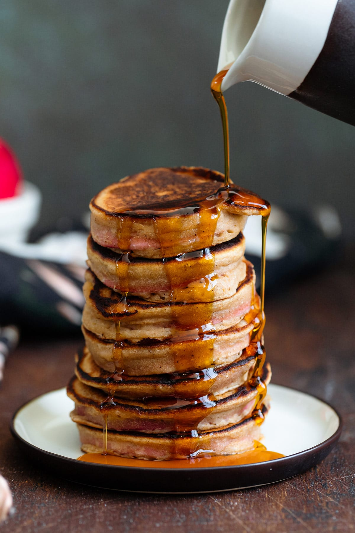 Maple syrup being poured over a stack of pancakes on a small plate on a dark wooden background.
