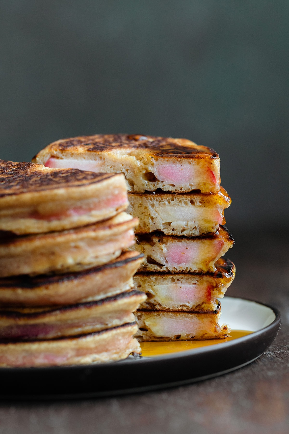 A stack of apple ring pancakes cut in half to see the inside drizzled with maple syrup.