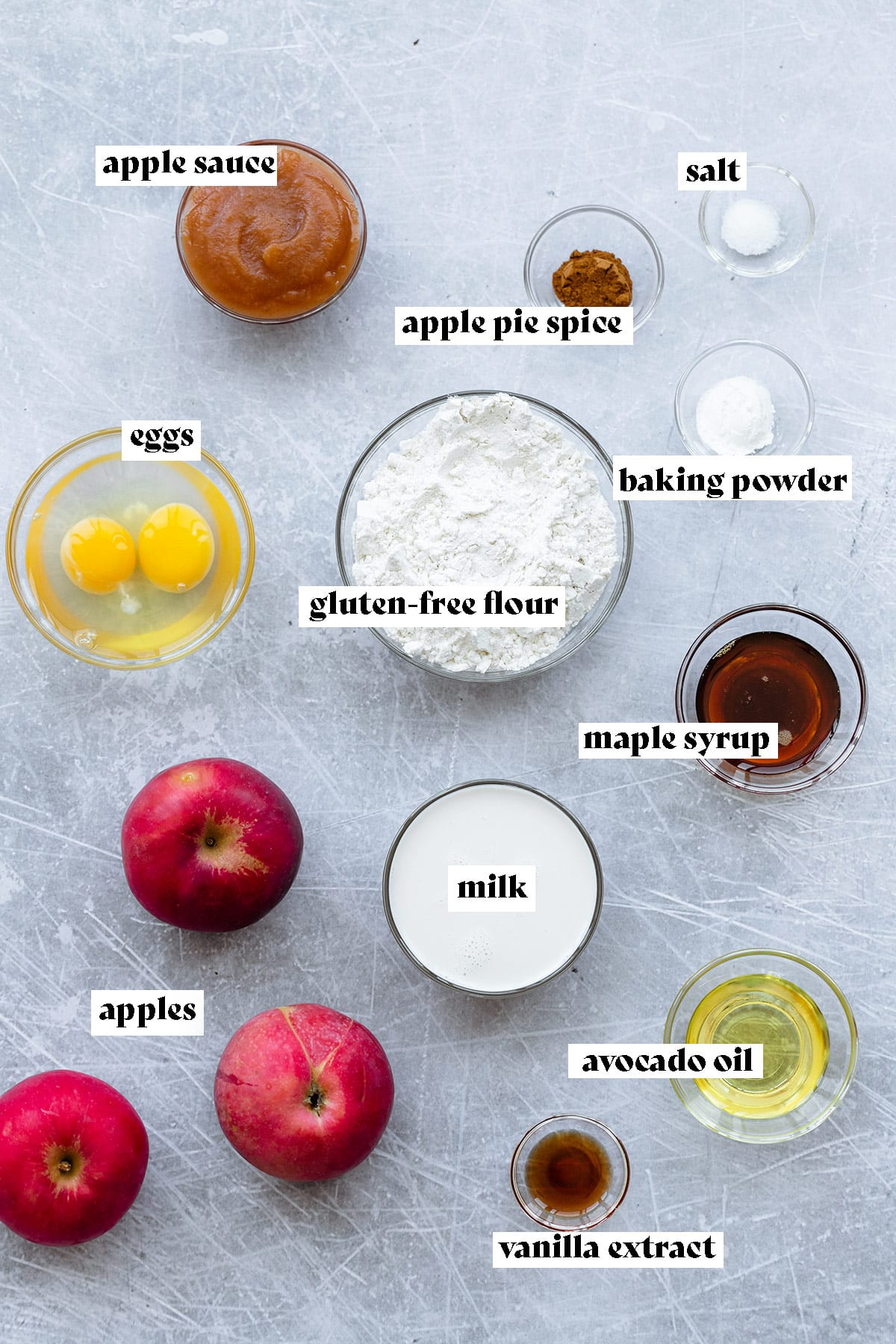 Ingredients for apple ring pancakes all laid out on a light metal background.