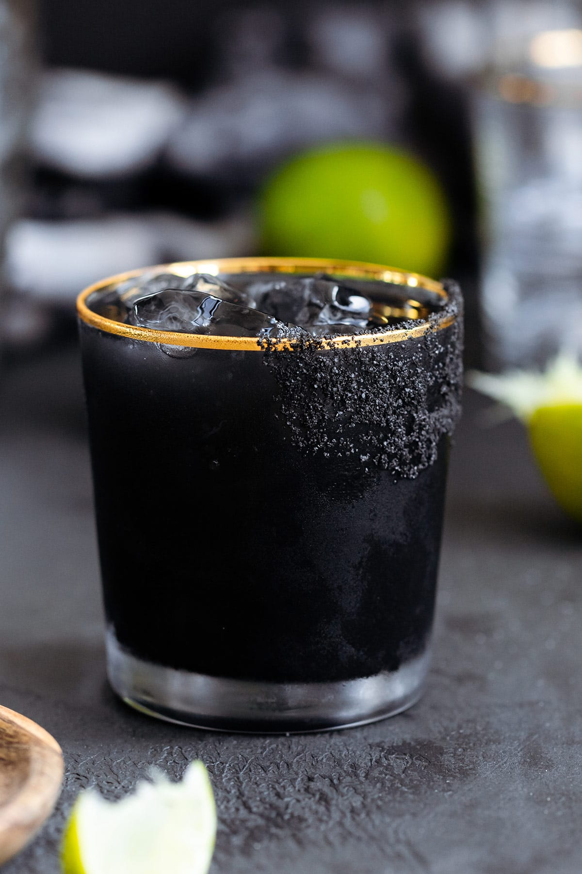 Black margarita with black salt rim on a black background with limes in the background.