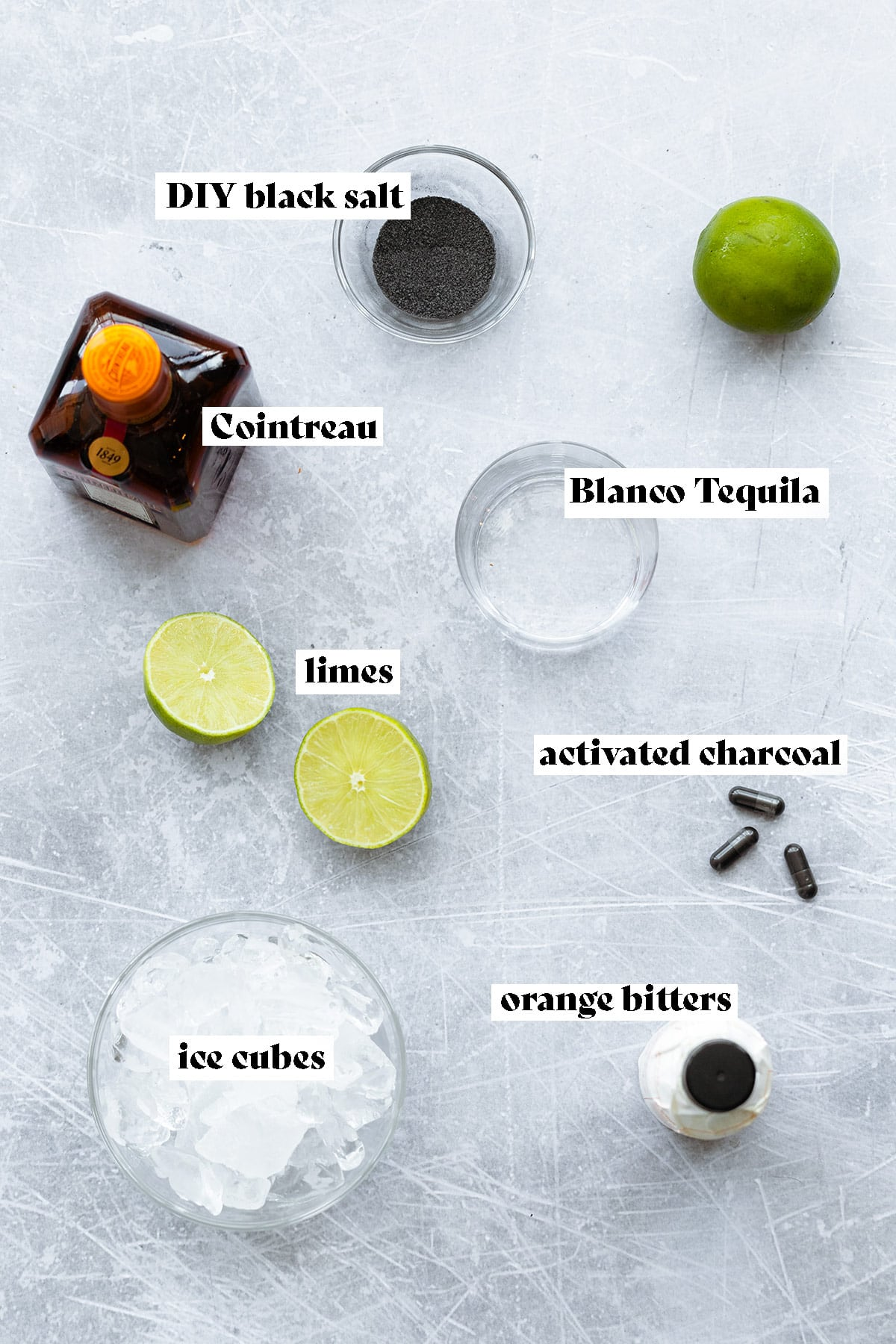 Ingredients for black margarita laid out on a light metal background.