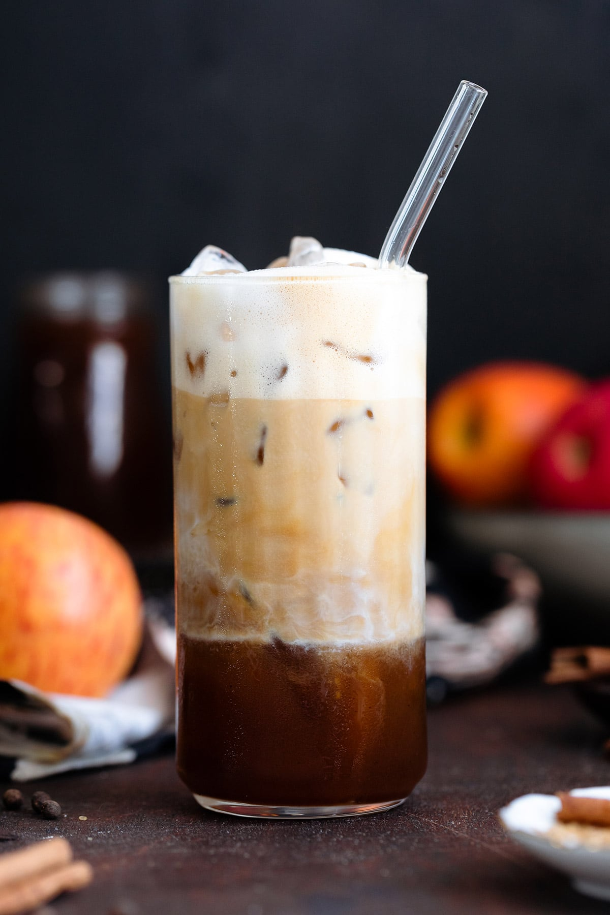 Espresso slowly mixing with frothy milk in a tall glass filled with ice.