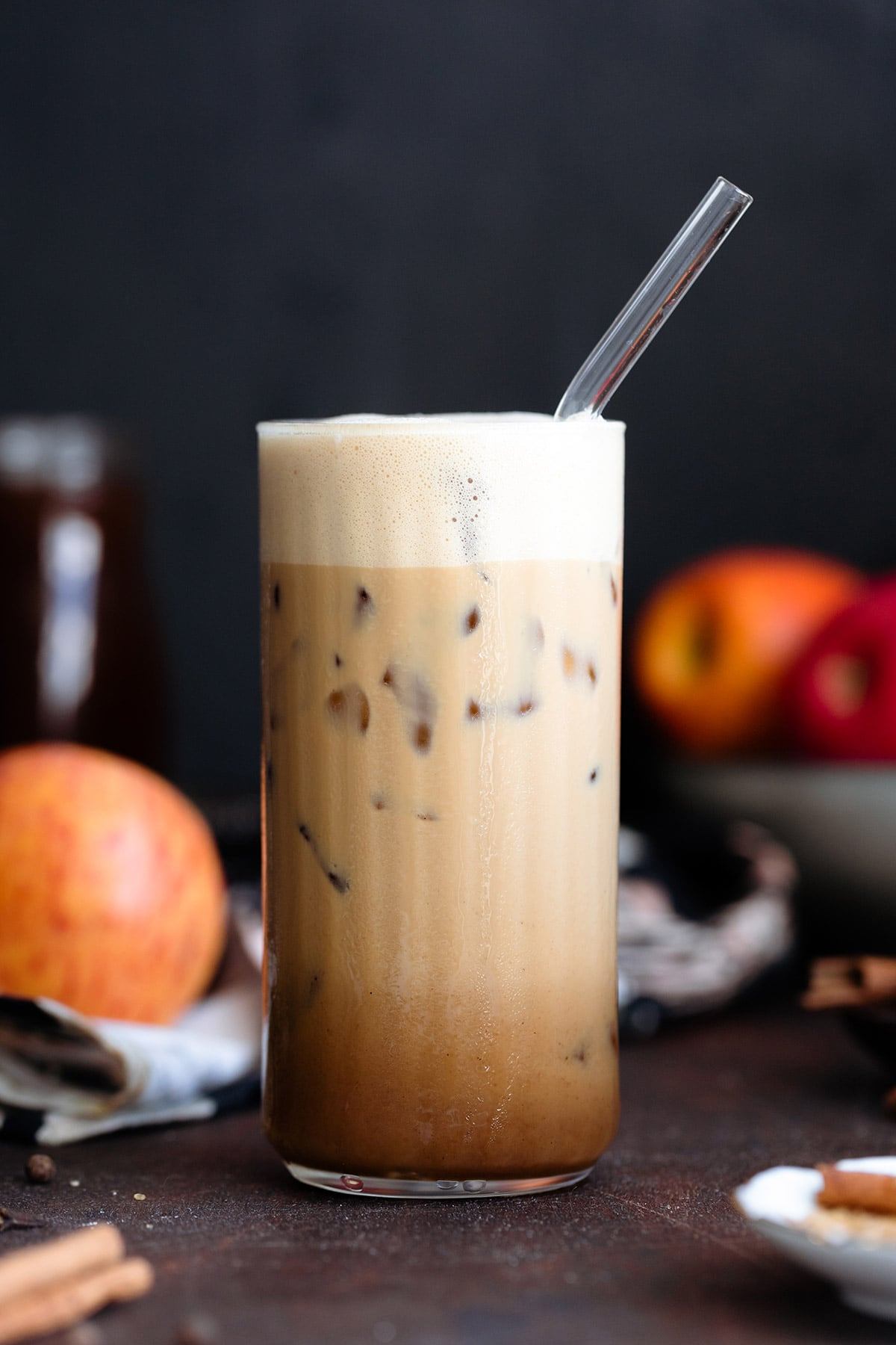 A tall glass with an iced macchiato on a dark background.