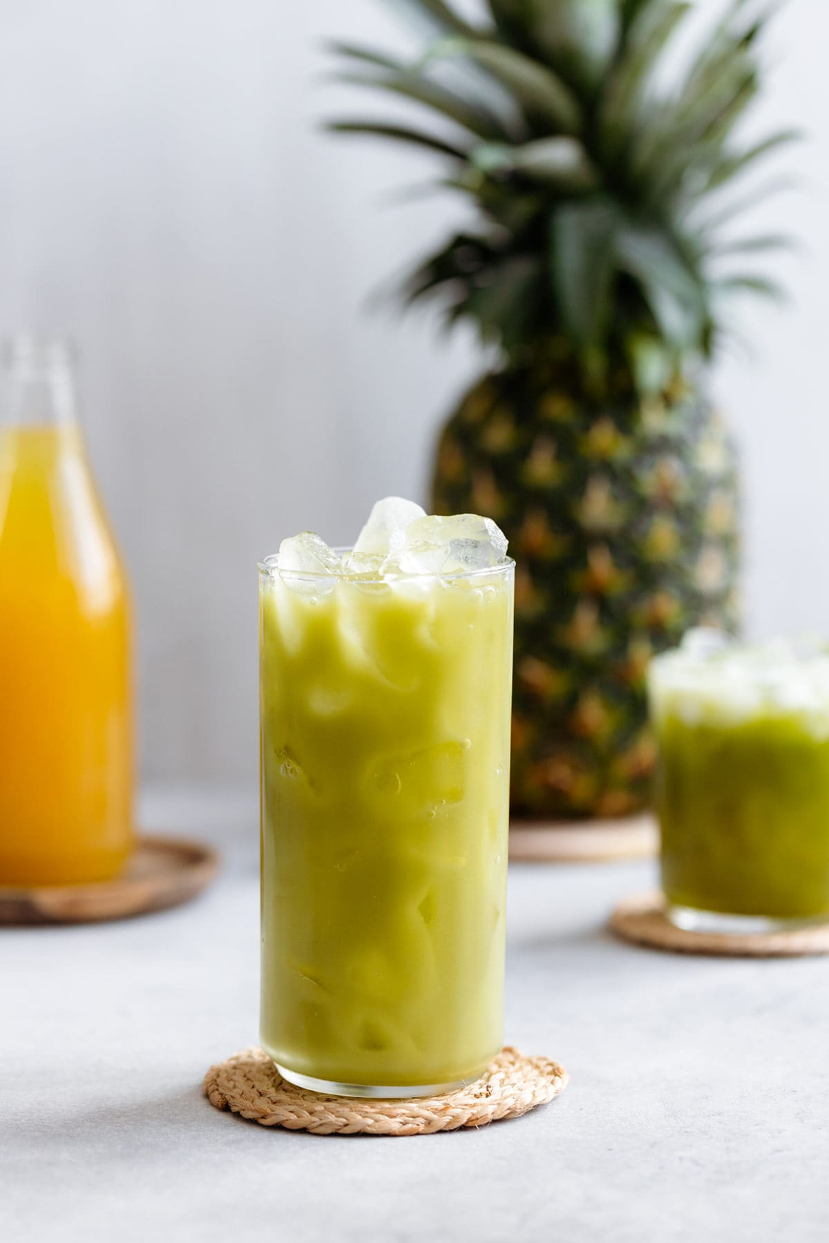 Pineapple drink in a tall glass served over ice on a white background with pineapple in the background.