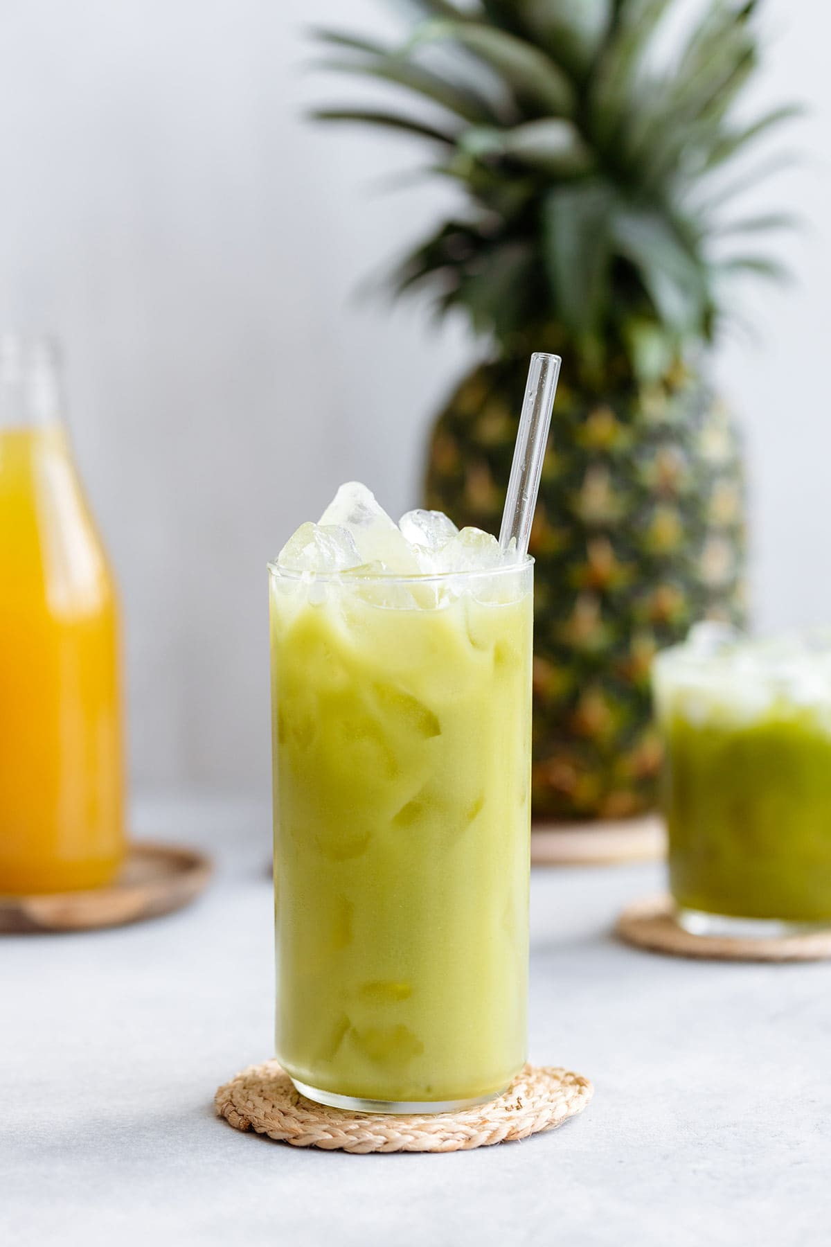 Pineapple drink in a tall glass served over ice and a glass straw.