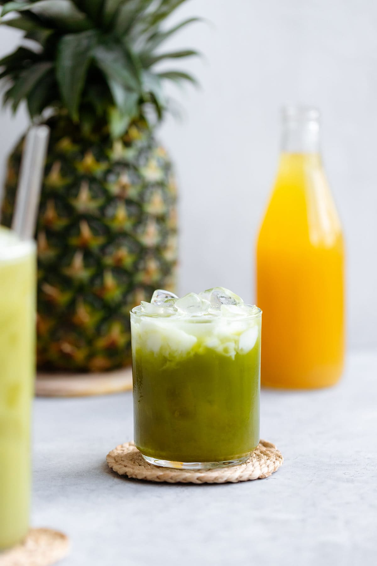 Pineapple matcha drink with coconut milk on top with ice in a short glass.