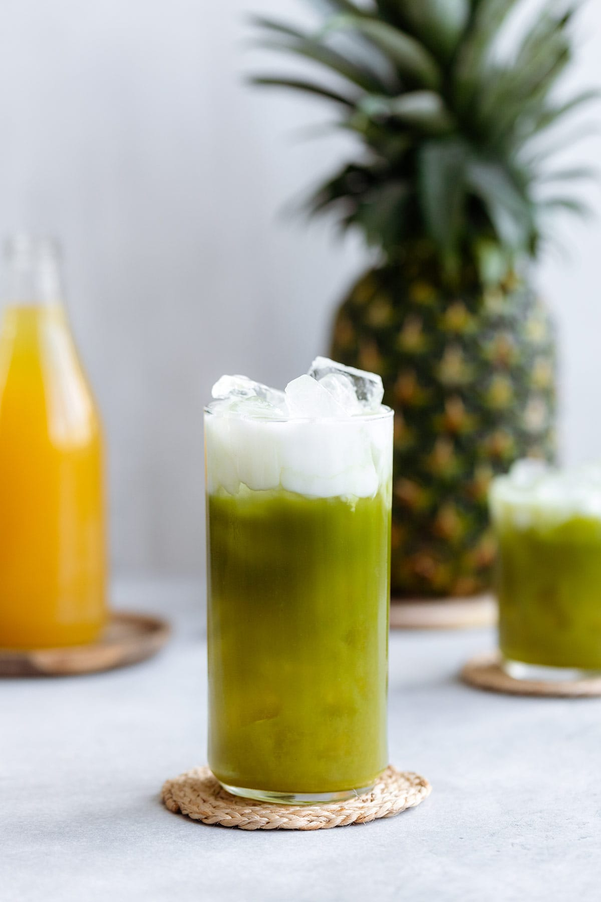 Pineapple matcha drink with coconut milk on top in a tall glass on a white background.