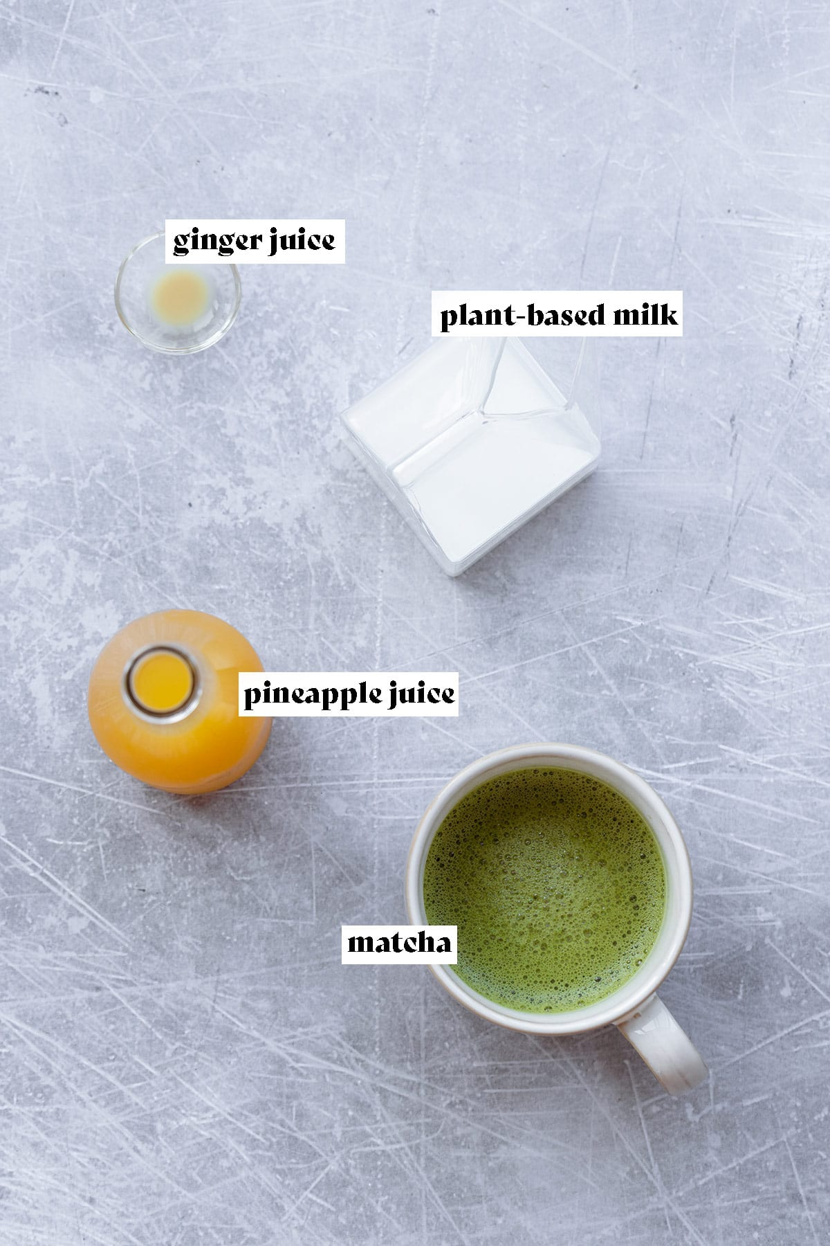 The four ingredients for Iced Pineapple Matcha Drink laid out on a light metal background.