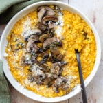 Pumpkin risotto topped with sauteed mushroom in a white plate on a light wooden background.